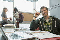 Portrait of smiling college student studying at table - HEROF01289