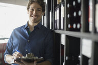Portrait of sommelier taking inventory in wine store - HEROF01295