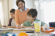 Smiling woman assisting son with homework - HEROF01313