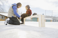 Father tying ice-skates for son - HEROF01499