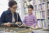 Mother and daughter reading book in bookstore - HEROF01649