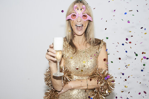 Senior woman wearing golden dress and flmingo shaped glasses, celebtraing New Year's Eve - IGGF00692