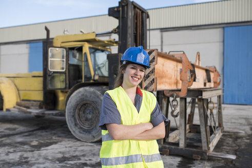 Portrait of confident female worker on industrial site near bulldozer - JASF02018