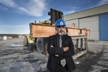 Confident businessman standing on industrial site near bulldozer with femaleworker in background - JASF02024