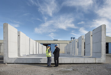 Businessman talking with female worker on industrial site in front of concrete blocks - JASF02027
