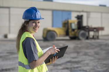 Portrait of smiling female worker with folder on industrial site - JASF02033