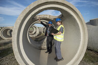 Businessman and female worker standing inside concrete pipe on industrial site - JASF02039