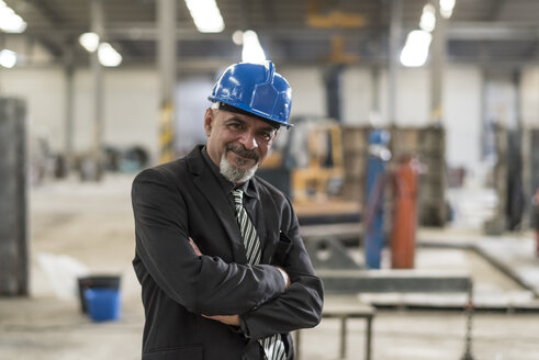Portrait of confident businessman wearing hard hat standing in a factory - JASF02045