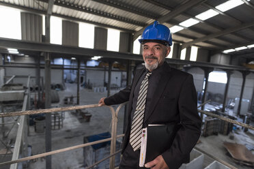 Portrait of confident businessman wearing hard hat standing in a factory - JASF02051