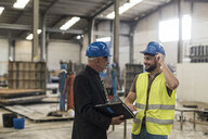 Businessman with folder talking to worker in factory - JASF02057
