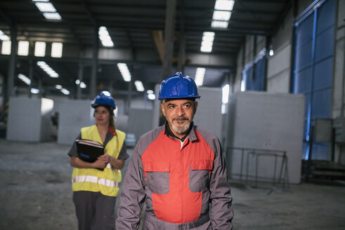 Male and female worker wearing hard hats in factory - JASF02060