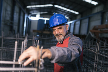 Portrait of confident worker wearing hard hat in factory checking rebar - JASF02063