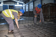 Male and female worker wearing hard hats working on rebar in factory - JASF02066