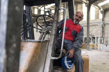 Portrait of worker sitting on forklift in factory - JASF02069