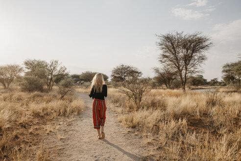 Africa, Namibia, blonde woman walking on way in grassland - LHPF00221