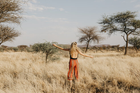 Africa, Namibia, blonde woman in grassland - LHPF00224