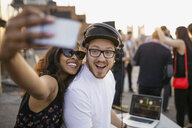 DJ and woman taking selfie at rooftop party - HEROF01703