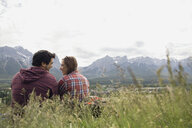 Couple sitting in grass with mountain view - HEROF01730