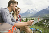 Couple looking at map in grass near mountains - HEROF01733