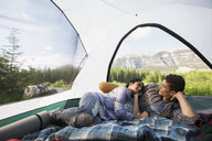 Couple laying in tent with mountain view - HEROF01784