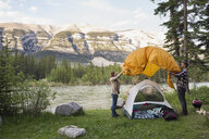 Couple assembling tent at campsite near mountains - HEROF01793