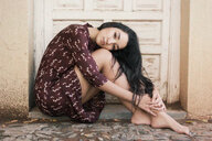 A beautiful young woman with long hair sitting by a doorstep - INGF10963
