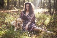 Portrait of a young woman with her dog sitting in the grass - INGF11032