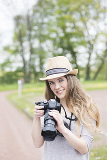 Portrait of smiling young woman comparing two different cameras outdoors - SKAF00084