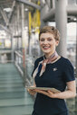 Portrait of smiling airline employee holding tablet at the airport - MFF04721