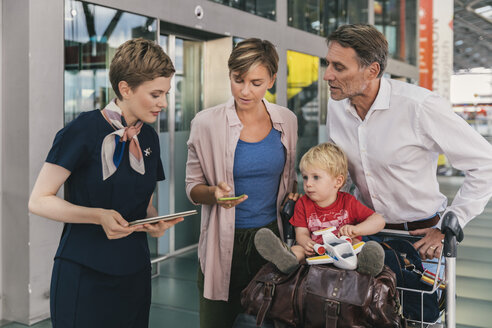 Airline employee assisting family with baggage cart at the airport - MFF04724