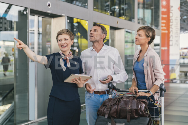Airline employee assisting couple with baggage cart at the airport - MFF04727