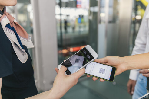 Airline employee scanning QR codes of passengers with smartphone at the airport - MFF04730