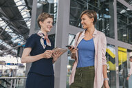 Airline employee with tablet and passenger with cell phone at the airport - MFF04736