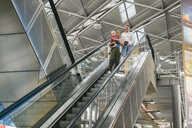 Family with small child going down escalator at CGN airport, Cologne, NRW, Germany - MFF04742