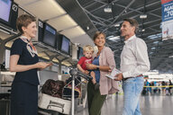 Happy family with airline employee at the airport check-in - MFF04748