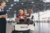 Travelling mother showing her young child around at the airport - MFF04754