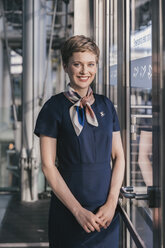 Portrait of smiling airline employee standing at the window at the airport - MFF04760