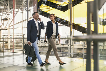 Businessman on cell phone and businesswoman walking at the airport - MFF04766