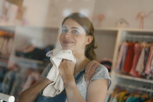 Smiling pregnant woman shopping for baby clothing in a boutique - KNSF05420