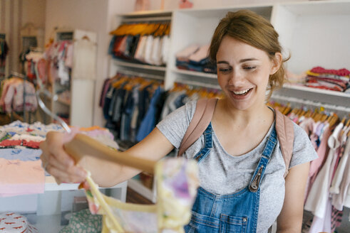 Happy pregnant woman shopping for baby clothing in a boutique - KNSF05429
