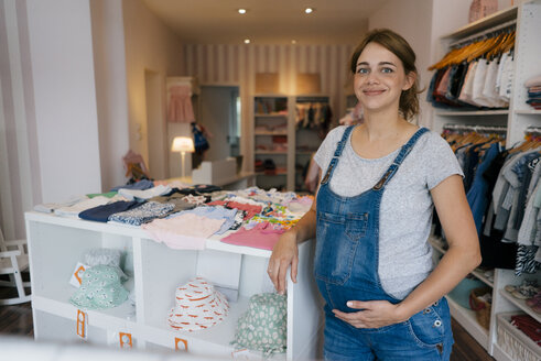 Portrait of smiling pregnant woman in a boutique for baby clothing - KNSF05432