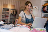 Pregnant woman using cell phone and laptop in a boutique for baby clothing - KNSF05435