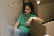 Exhausted pregnant woman sitting on floor surrounded by cardboard boxes - KNSF05444
