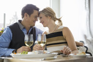 Affectionate couple enjoying white wine at bistro table - HEROF01879