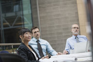 Business people listening attentively in conference room meeting - HEROF01882