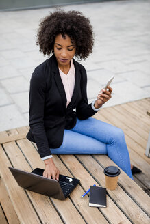Businesswoman sitting on table outdoors using laptop and smartphone - MAUF01979
