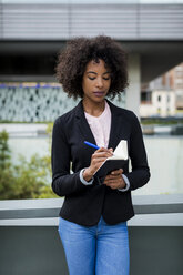 Portrait of businesswoman taking notes outdoors - MAUF01994