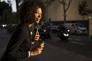 Portrait of businesswoman with coffee to go and cell phone waiting at evening twilight - MAUF02000