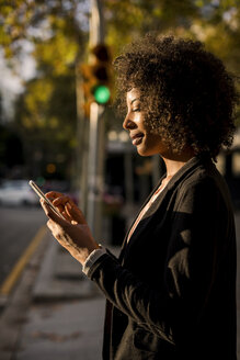 Smiling businesswoman using cell phone on the street at evening twilight - MAUF02003