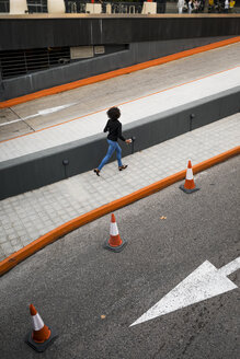 Back view of businesswoman running on pavement - MAUF02009